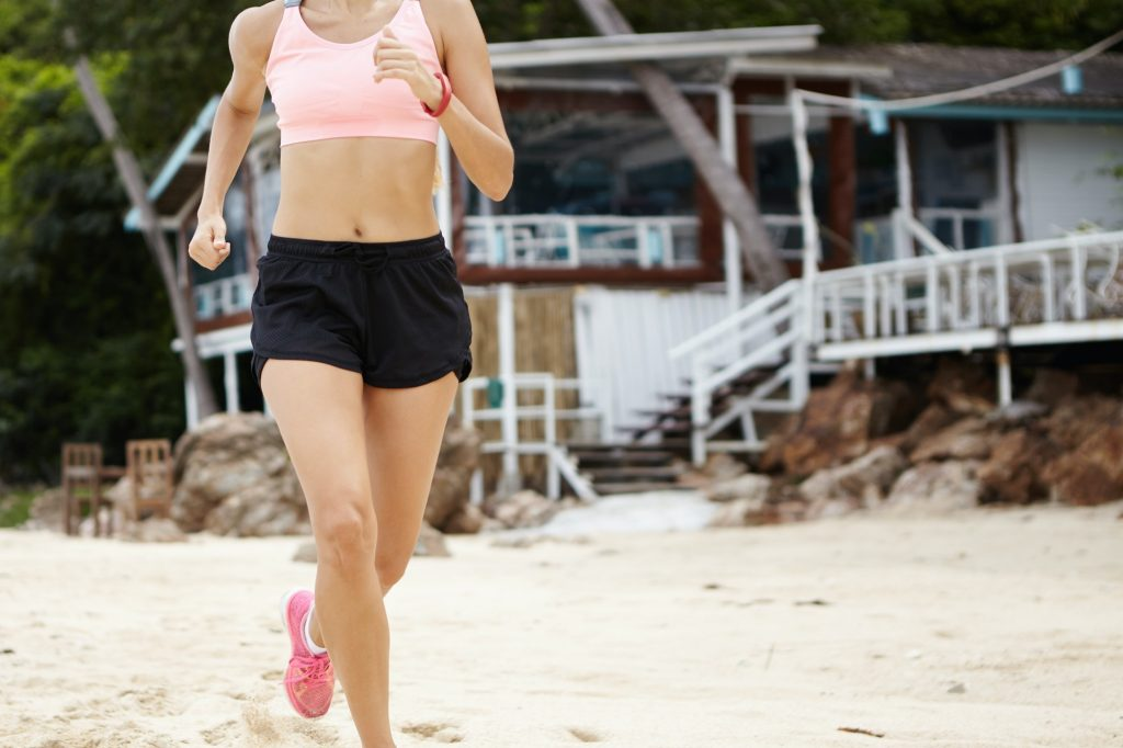 Motivation, determination and endurance. Cardio running workout. Unrecognizable woman runner in moti