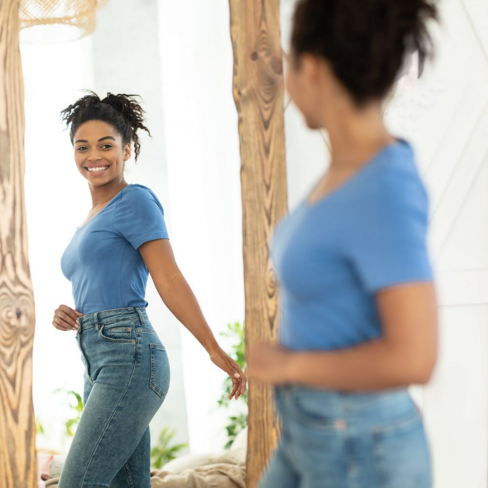 Woman looking in the mirror feeling happy with her appearance
