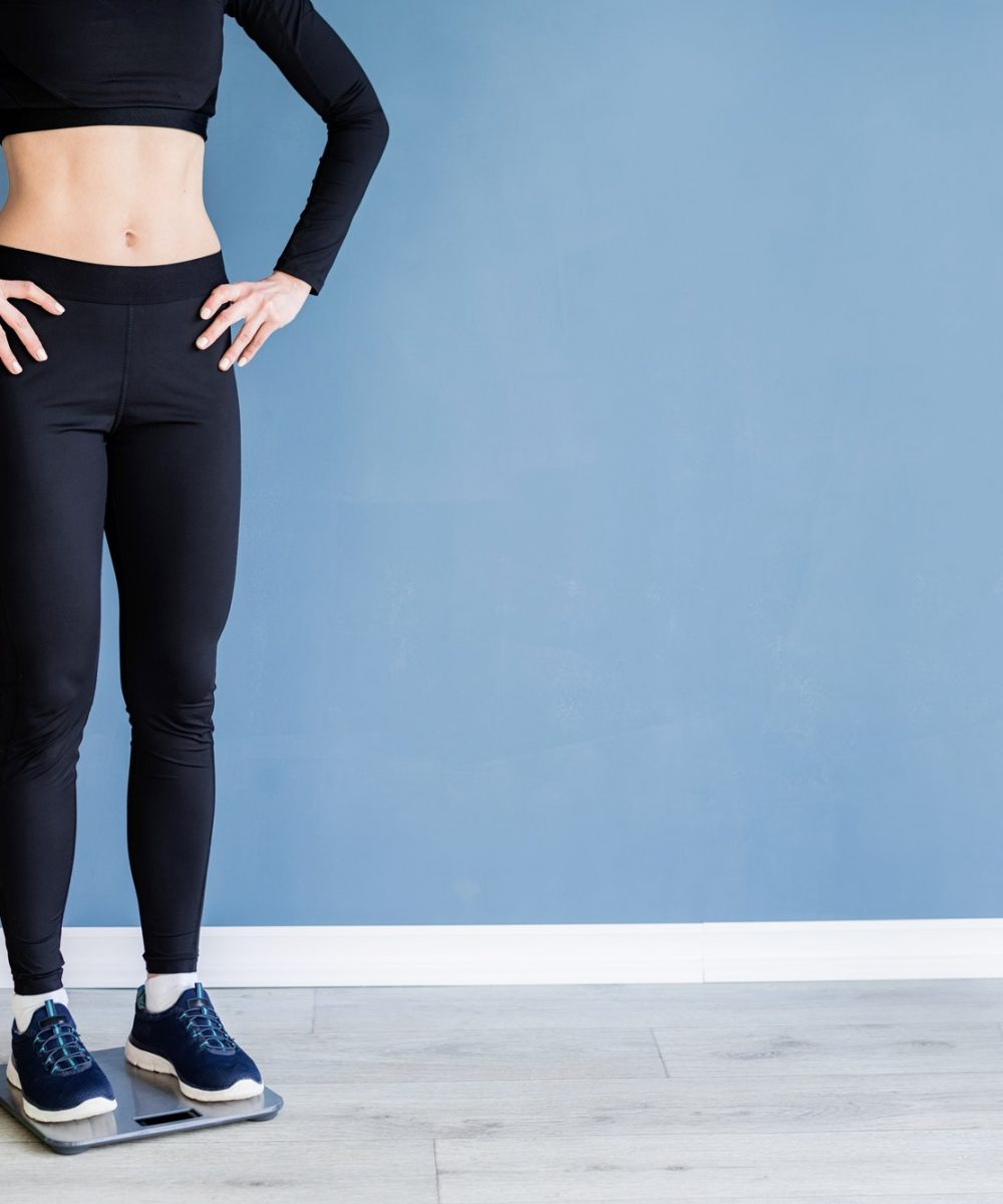 woman in black sport clothes standing on scales